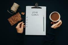 Las metas de la visión superior 2018 enumeran con las manos de la mujer, lápiz, chocolate, co Fotografía de archivo libre de regalías