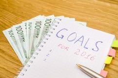 Las metas del año 2016 escriben en el cuaderno con la pluma y el euro Foto de archivo