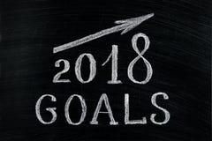 Las metas del Año Nuevo 2018 con un texto de levantamiento de la flecha marcan con tiza en un blackboa Foto de archivo libre de regalías