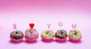 Las mini tortas con la congelación y colorido asperja en el fondo rosado, texto te amo imagenes de archivo