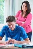 Las miradas de la madre que desaprueban como hijo adolescente utilizan el teléfono móvil Whils Fotografía de archivo