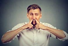 Las miradas de la nariz de los pellizcos del hombre con repugnancia algo apestan el mún olor fotografía de archivo