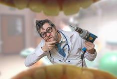 Las miradas locas del doctor del dentista en boca y los controles perforan Foto de archivo libre de regalías