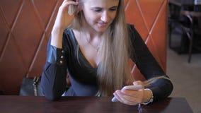 Las miradas rubias de la mujer alegre en el teléfono móvil se sientan en Sofa Behind Table metrajes