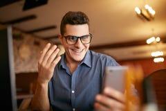 Las miradas sorprendidas del hombre del inconformista del freelancer al smartphone y no pueden creer que él ganó el premio o el d Imágenes de archivo libres de regalías