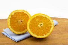 Las mitades anaranjadas cortadas en naptkin y madera azules suben Foto de archivo