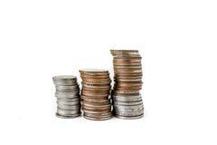 Las monedas apilan en el fondo blanco Foto de archivo