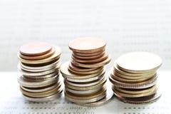 Las monedas apilan en el libro de cuentas de ahorro o el estado financiero Imagen de archivo libre de regalías
