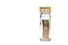 Las monedas apilan en la botella de cristal Fotografía de archivo libre de regalías
