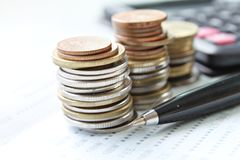 Las monedas apilan, pluma y calculadora en el libro de cuentas de ahorro o el estado financiero Imagen de archivo
