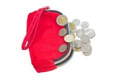 Las monedas caen abajo de la cartera roja. foto de archivo libre de regalías