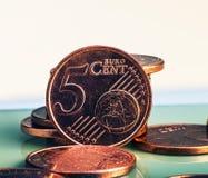 Las monedas cinco centavos euro mienten en una pila de monedas Monedas en el blurr Fotos de archivo libres de regalías