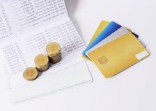 Las monedas de la tarjeta y del dinero de crédito apilan en el banco del libro para el dinero co del préstamo fotografía de archivo libre de regalías