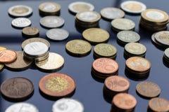 Las monedas de los países diferentes se presentan en pilas en un fondo azul imagenes de archivo