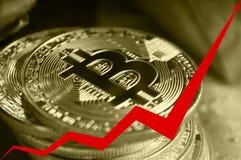 Las monedas de oro de bitcoins, la flecha roja del gráfico se dirigen hacia arriba Imagenes de archivo