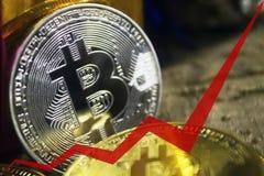 Las monedas de oro de bitcoins, la flecha roja del gráfico se dirigen hacia arriba Imagen de archivo