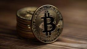 Las monedas de oro del efectivo de Bitcoin mienten en la superficie de madera Cierre para arriba almacen de metraje de vídeo