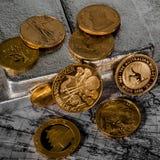 Las monedas de oro del mundo se sientan en las barras de plata Imágenes de archivo libres de regalías