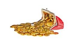 Las monedas de oro dispersadas están en el monedero rojo, aislado en el backg blanco Imágenes de archivo libres de regalías