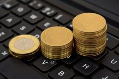 Las monedas de oro representan la subida gráficamente en el comercio en línea del teclado Imágenes de archivo libres de regalías