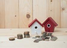 Las monedas del dinero apilan el crecimiento con la casa roja en el fondo de madera megabus imágenes de archivo libres de regalías