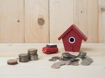 Las monedas del dinero apilan el crecimiento con la casa roja en el fondo de madera megabus imagen de archivo