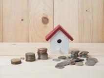 Las monedas del dinero apilan el crecimiento con la casa roja en el fondo de madera megabus fotos de archivo libres de regalías
