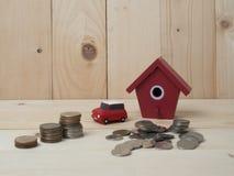Las monedas del dinero apilan el crecimiento con la casa roja en el fondo de madera megabus fotografía de archivo