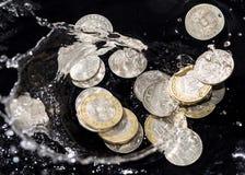 Las monedas en agua salpican en un fondo negro Imagen de archivo libre de regalías