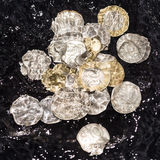 Las monedas en agua salpican en un fondo negro Fotos de archivo