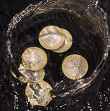 Las monedas en agua salpican en un fondo negro Foto de archivo libre de regalías