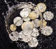 Las monedas en agua salpican en un fondo negro Imagenes de archivo
