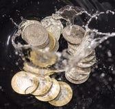 Las monedas en agua salpican en un fondo negro Fotografía de archivo