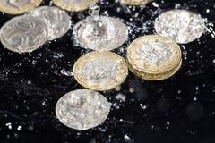 Las monedas en agua salpican en un fondo negro Foto de archivo