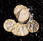 Las monedas en agua salpican en un fondo negro Imágenes de archivo libres de regalías