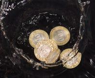 Las monedas en agua salpican en un fondo negro Imagen de archivo