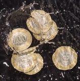 Las monedas en agua salpican en un fondo negro Fotos de archivo libres de regalías