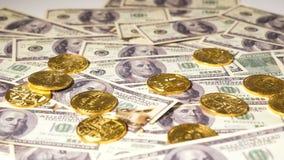 Las monedas en billetes de banco de los dólares pertenecen a la moneda virtual Bitcoin almacen de metraje de vídeo