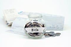 Las monedas en el envase de cristal con la etiqueta de las cuentas con los recibos de las cuentas son Imagenes de archivo