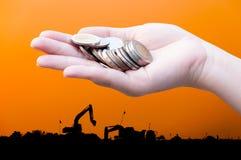 Las monedas en manos en silueta de la industria ajardinan el fondo Imagenes de archivo