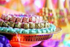 Las monedas en ribbin colorido en un oro ruedan para los monjes budistas nuevamente ordenados Fotografía de archivo