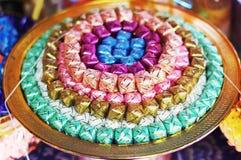 Las monedas en ribbin colorido en un oro ruedan para los monjes budistas nuevamente ordenados Fotografía de archivo libre de regalías