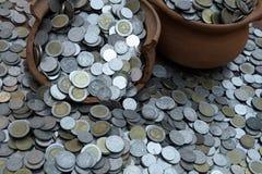 Las monedas en tarro quebrado en de porciones de la pila acuñan con el fondo borroso, la pila del dinero para la inversión de la  imágenes de archivo libres de regalías