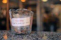 Las monedas en un envase de cristal con una etiqueta ejercen la actividad bancaria Fotografía de archivo libre de regalías