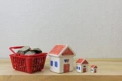 Las monedas en un rojo y una casa de la cesta modelan Fotografía de archivo
