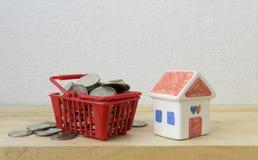 Las monedas en un rojo y una casa de la cesta modelan Foto de archivo libre de regalías