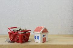 Las monedas en un rojo y una casa de la cesta modelan Foto de archivo