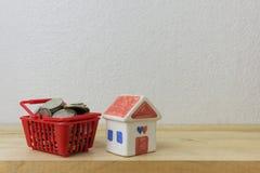 Las monedas en un rojo y una casa de la cesta modelan Imagenes de archivo