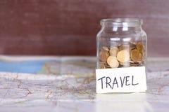 Las monedas en un tarro con viaje firman en un mapa contra el marrón w del vintage Foto de archivo
