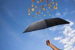 Las monedas están lloviendo sobre un paraguas Imagen de archivo libre de regalías